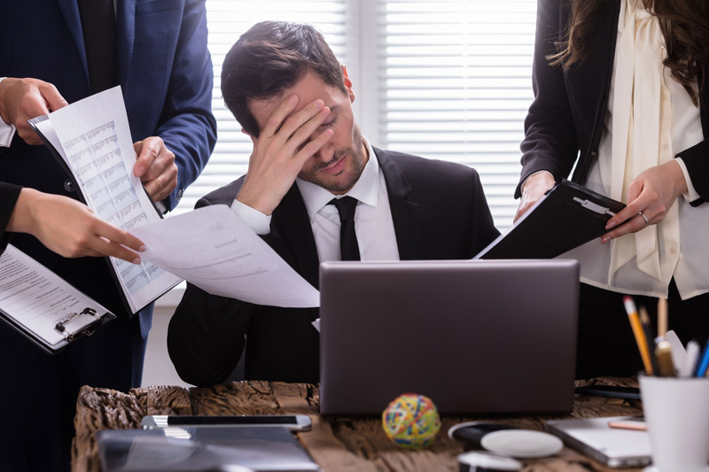 A man looking frustrated as three people hand him paperwork